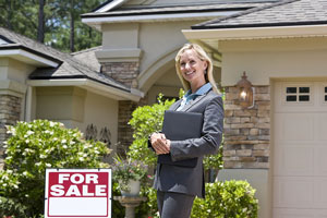real estate agent posing in front of a house for sale